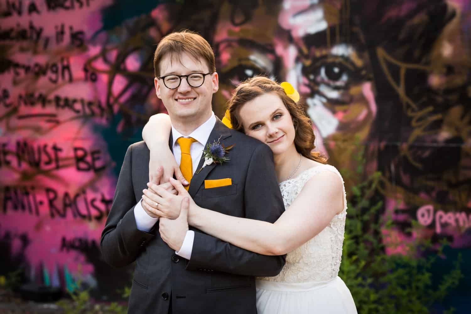 Bride hugging groom in front of graffiti for an article on Covid-19 wedding planning
