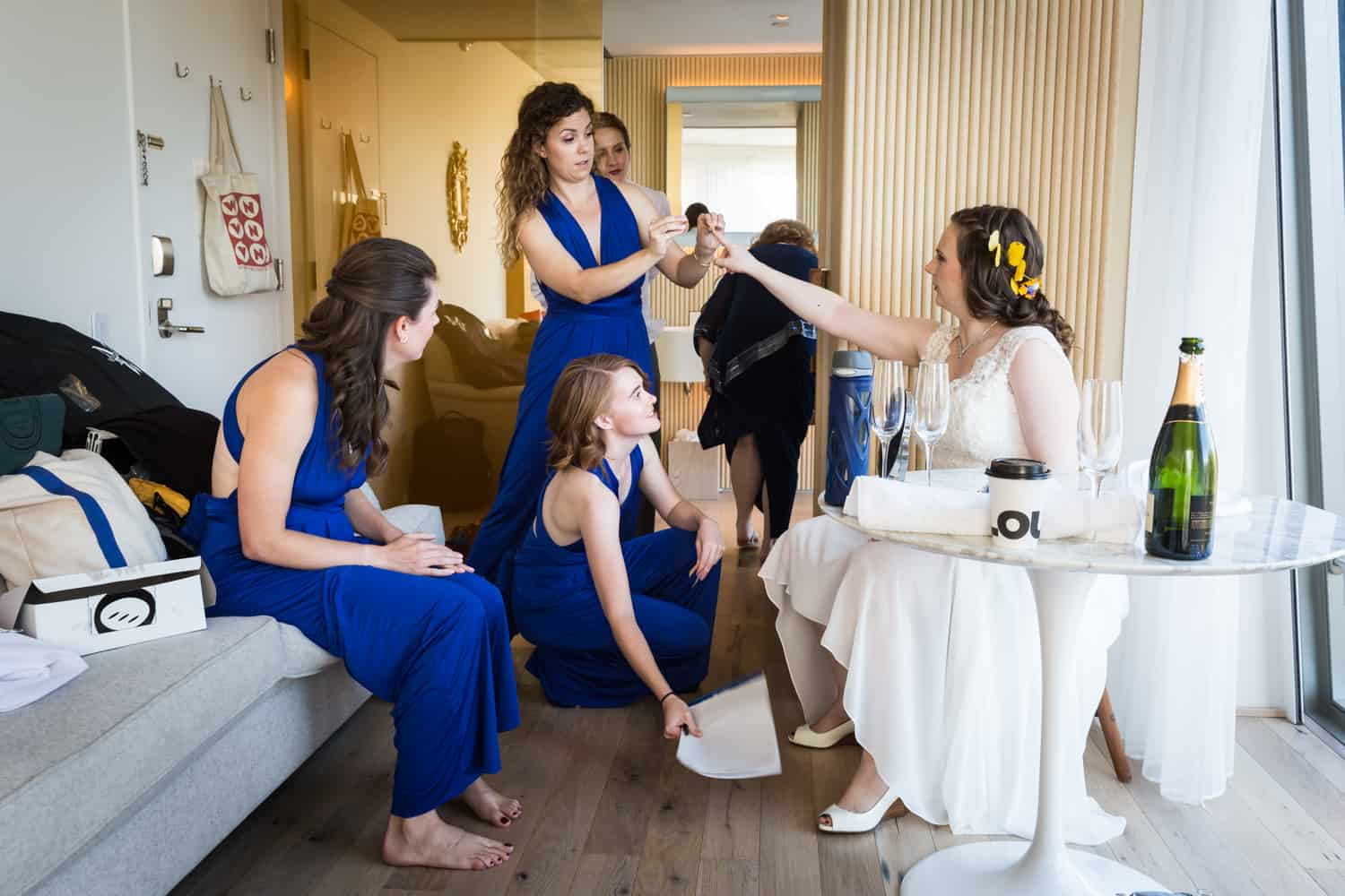 Bride in hotel room being attended by bridesmaids