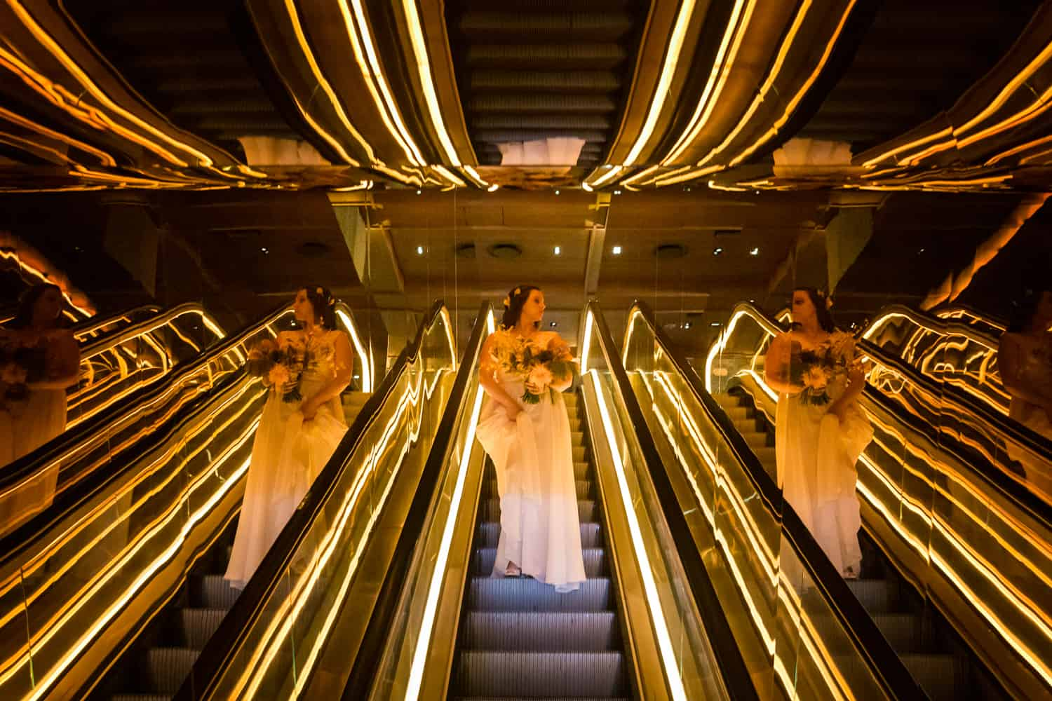 Bride coming down neon-lit escalator