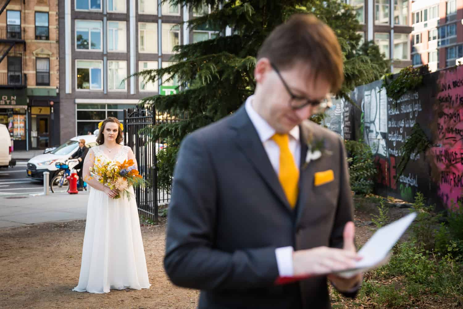 Groom reading letter with bride behind him