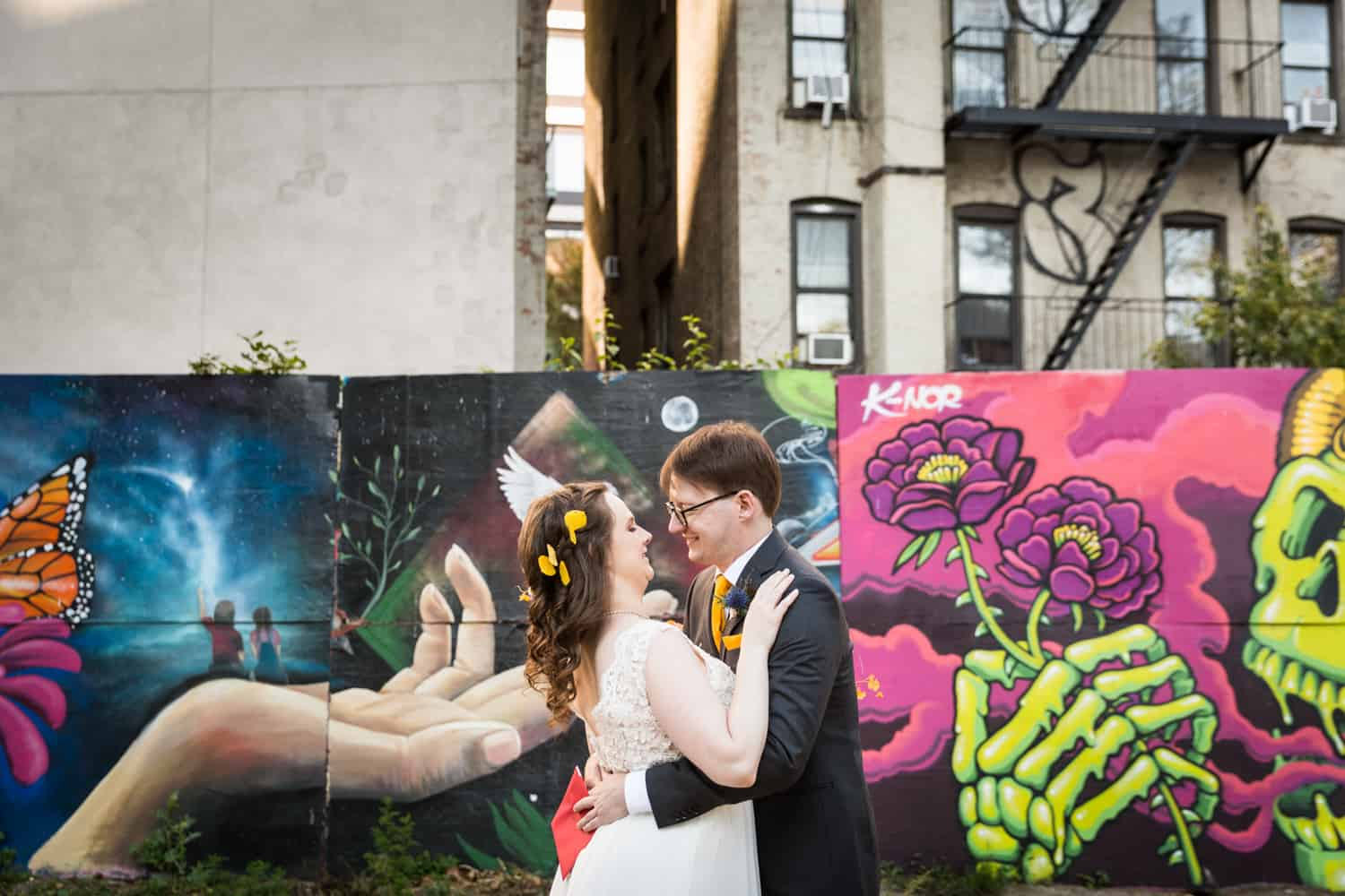 Bride and groom hugging in front of graffiti for an article on Covid-19 wedding planning