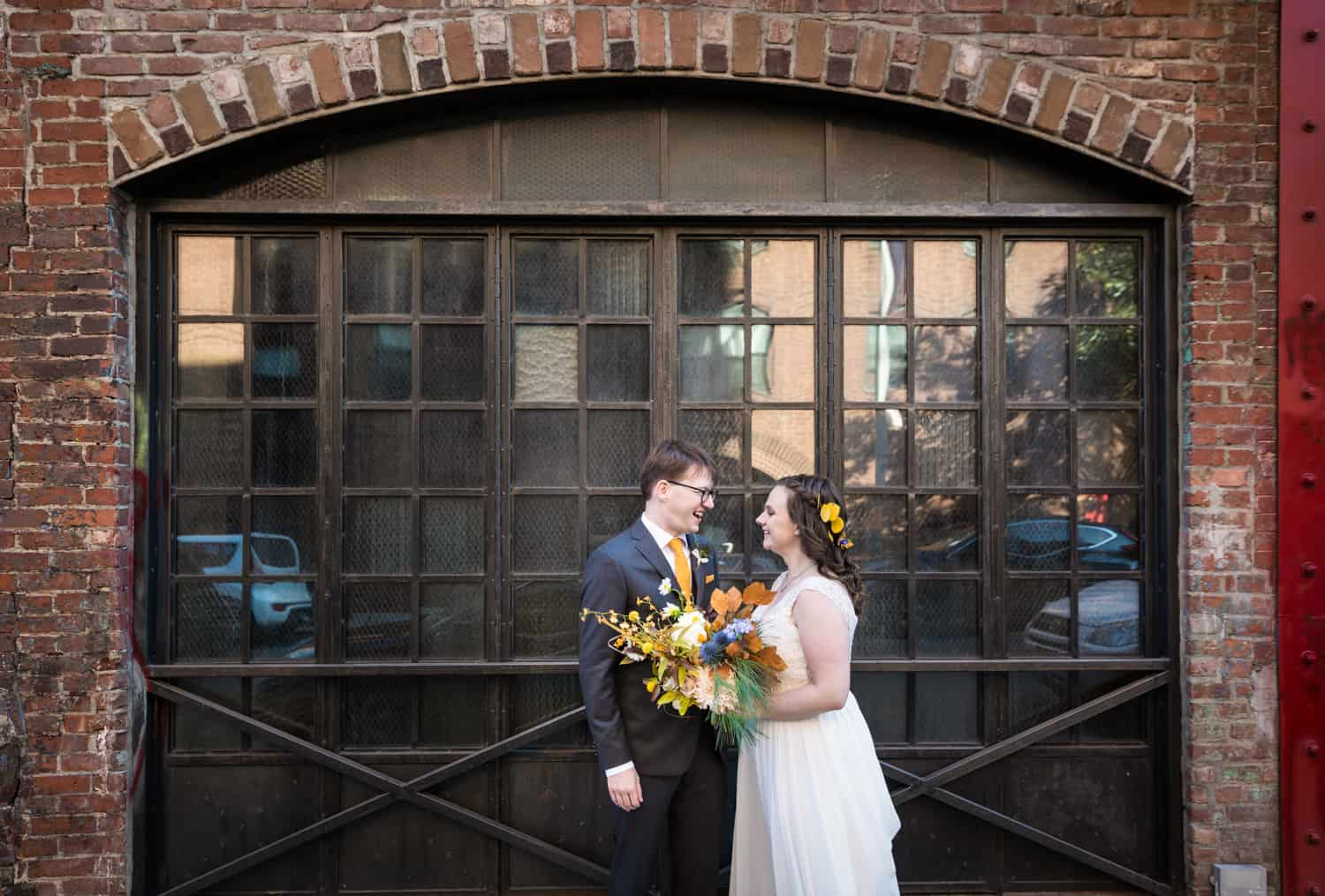 Bride and groom in front of arched window for an article on Covid-19 wedding planning