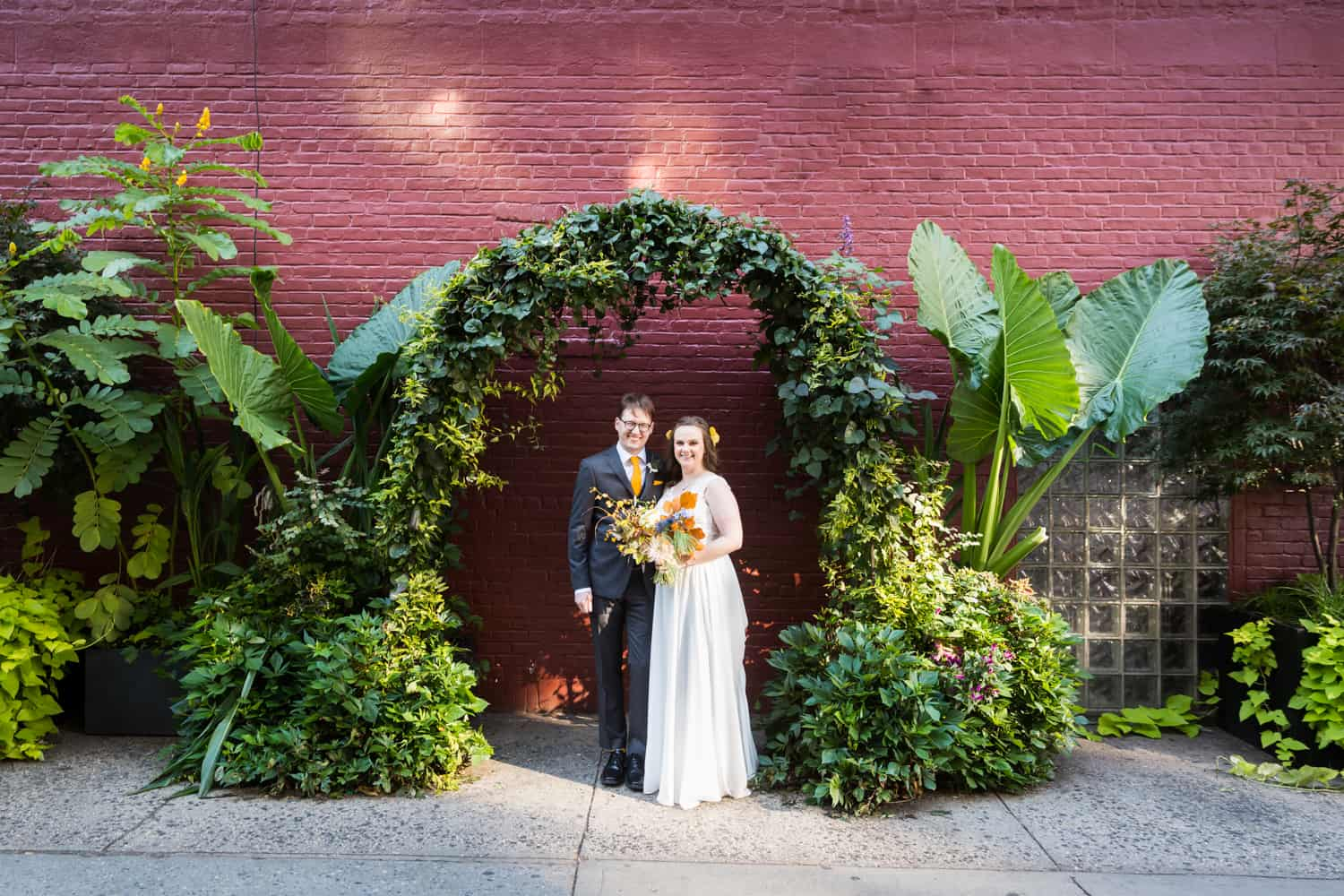 Bride and groom under arch of plants on NYC sidewalk