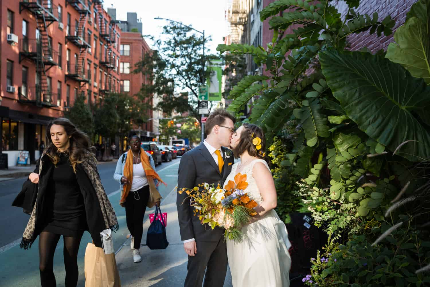 Bride and groom kissing on sidewalk for an article on Covid-19 wedding planning