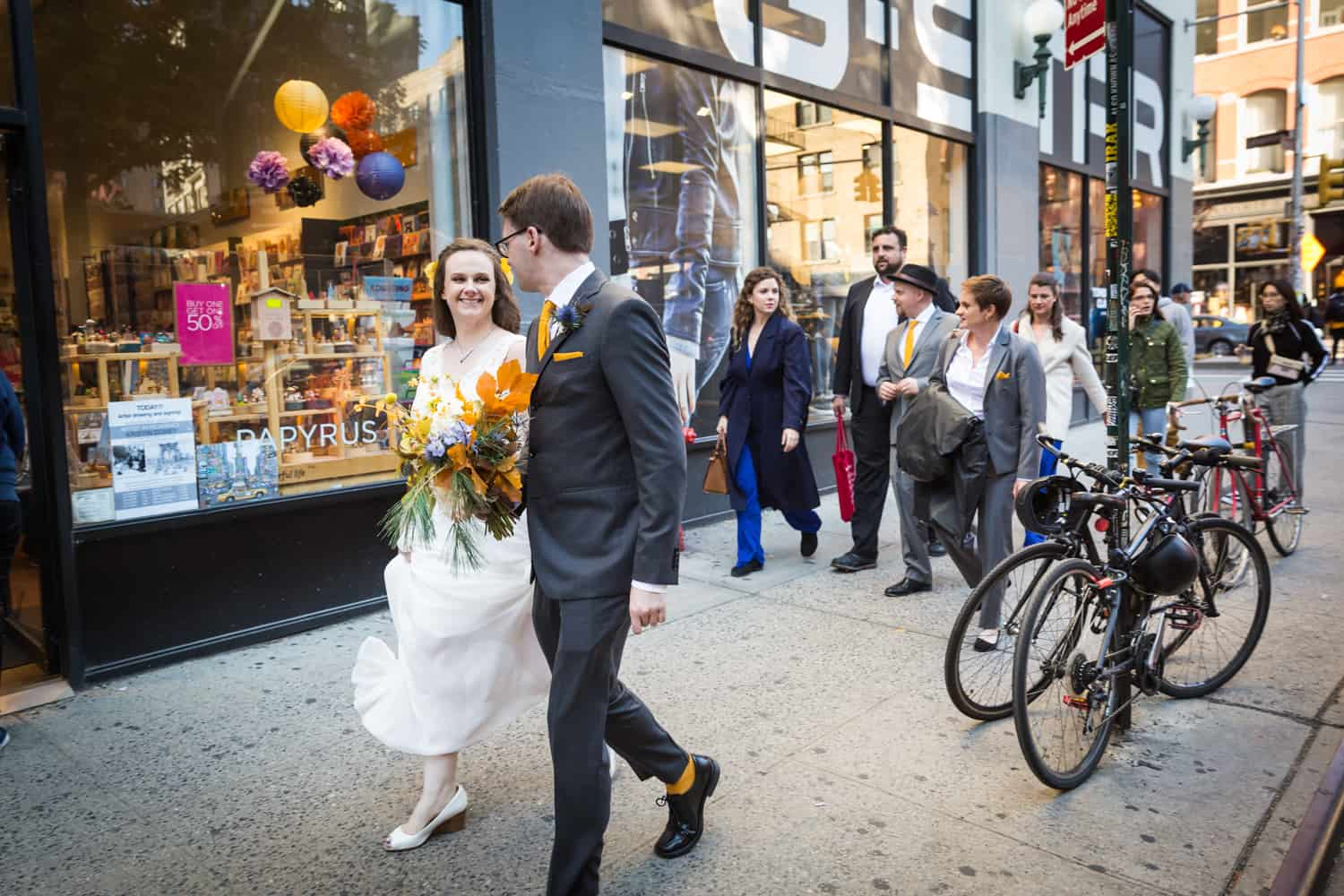 Bride and groom walking in front of bridal party on NYC sidewalk