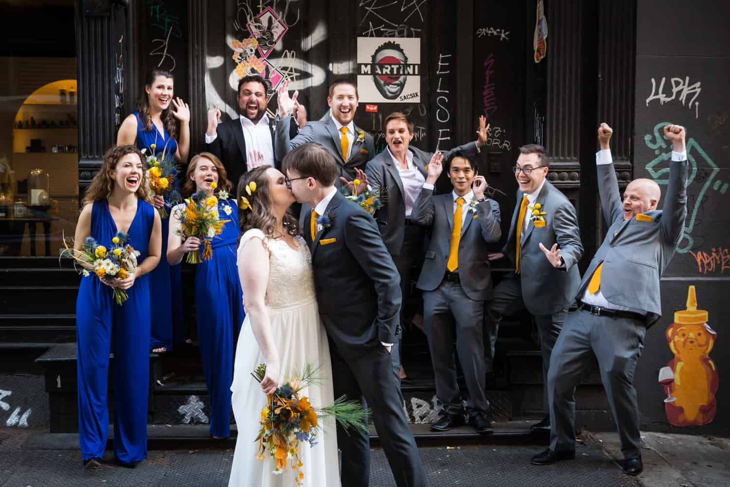 Bridal party cheering as bride and groom kiss for an article on Covid-19 wedding planning