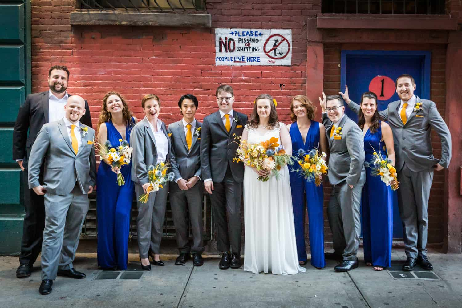 Bridal party standing in front of sign for an article on Covid-19 wedding planning