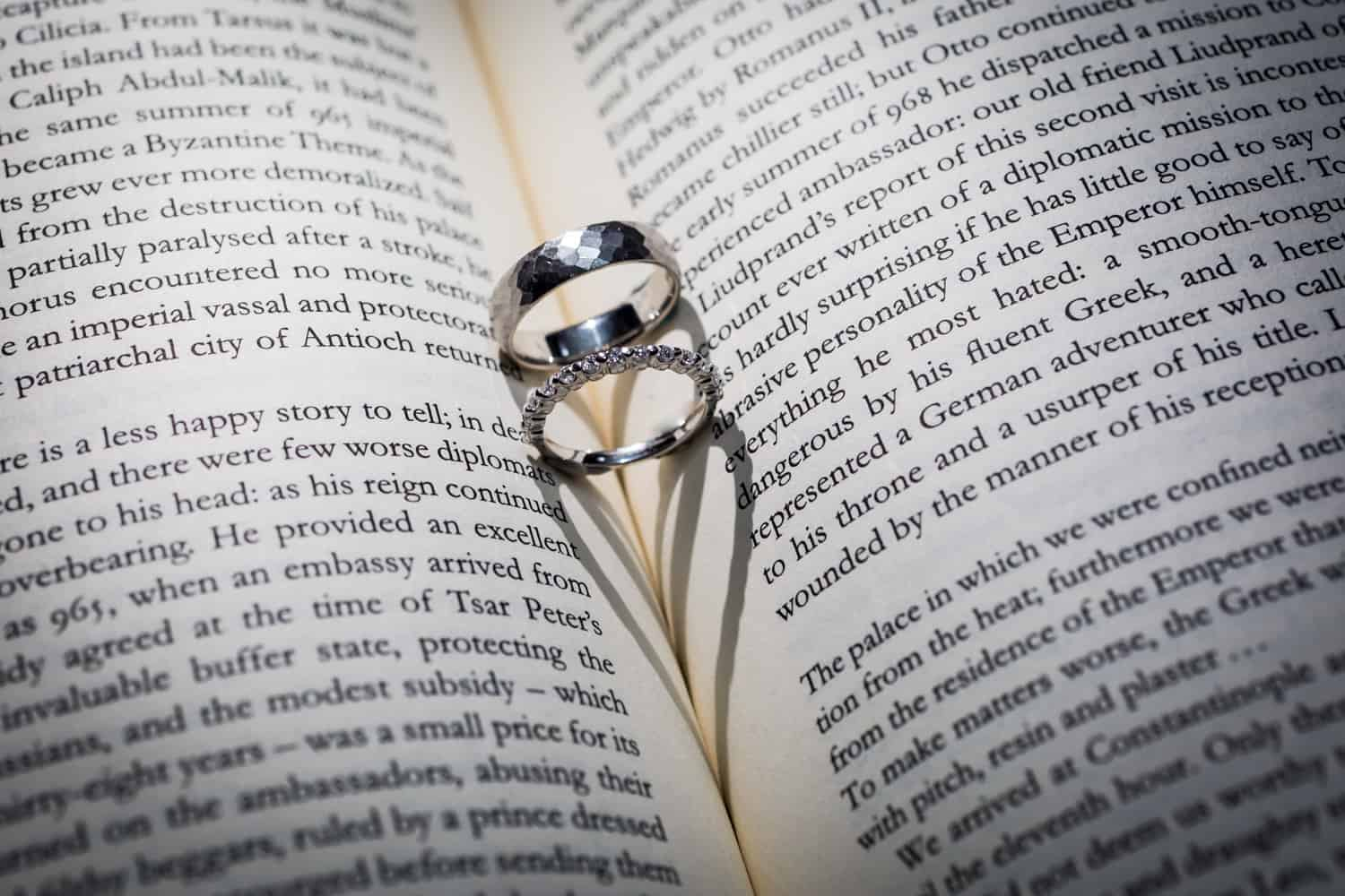 Wedding rings in center of book with heart-shaped shadow