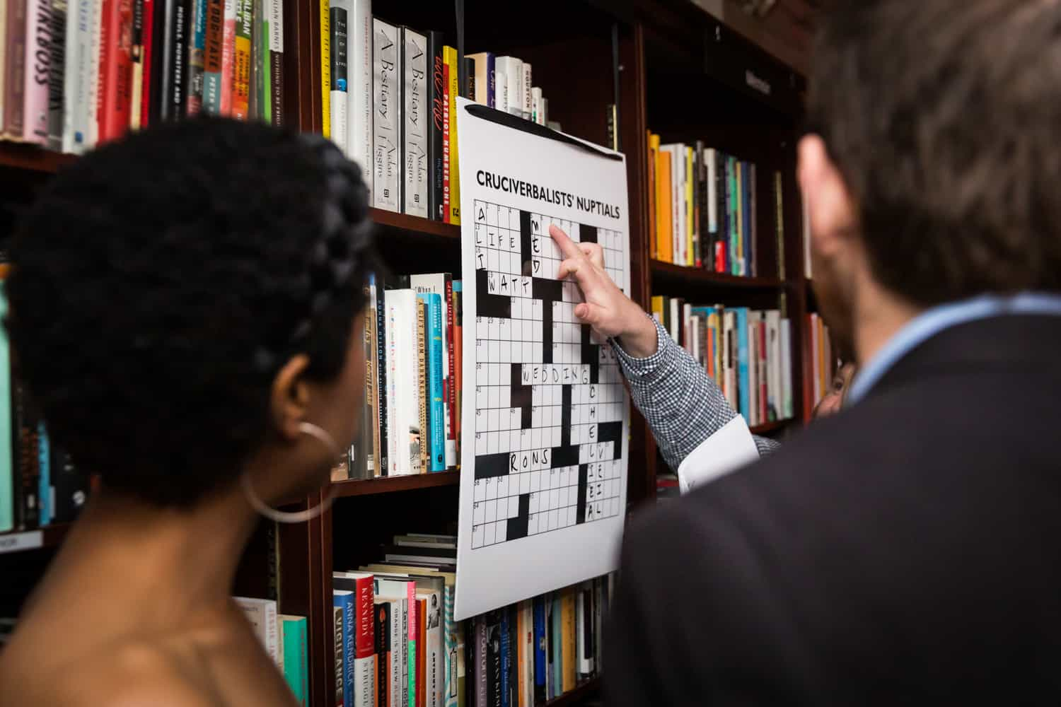 Guests pointing to crossword puzzle hanging on bookcase