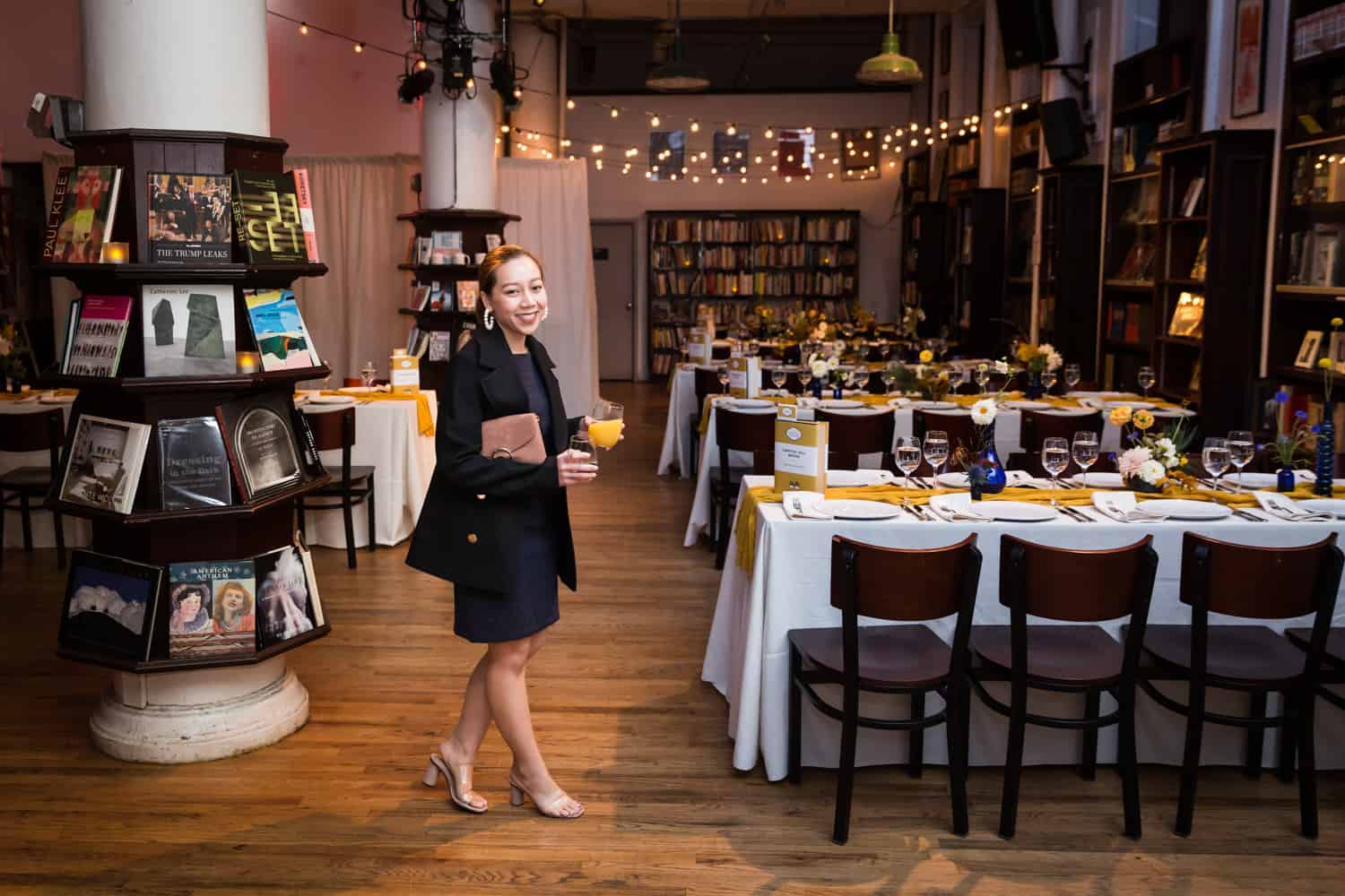 Female guest standing in front of tables at a Housing Works Bookstore Cafe wedding