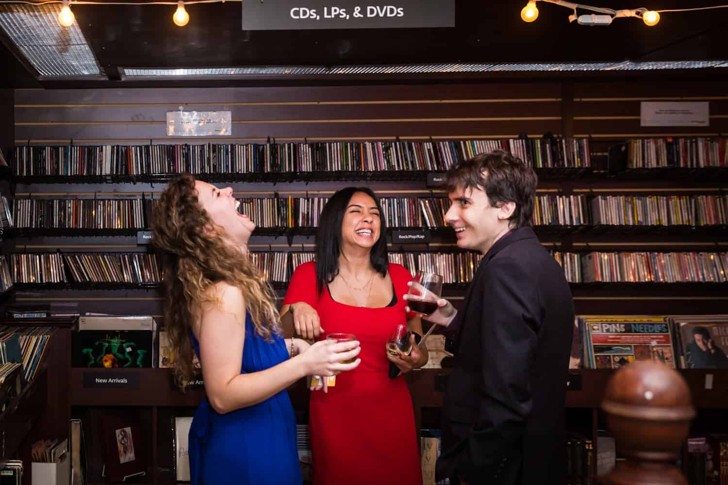Three guests laughing in front of rows of CDs at a Housing Works Bookstore Cafe wedding
