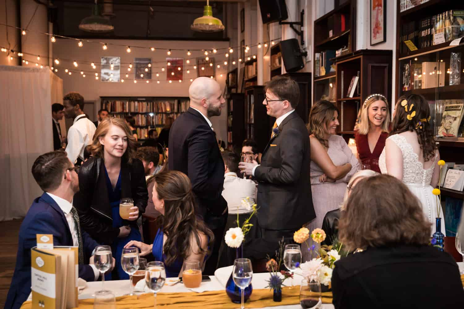 Guests chatting with bride and groom at a Housing Works Bookstore Cafe wedding