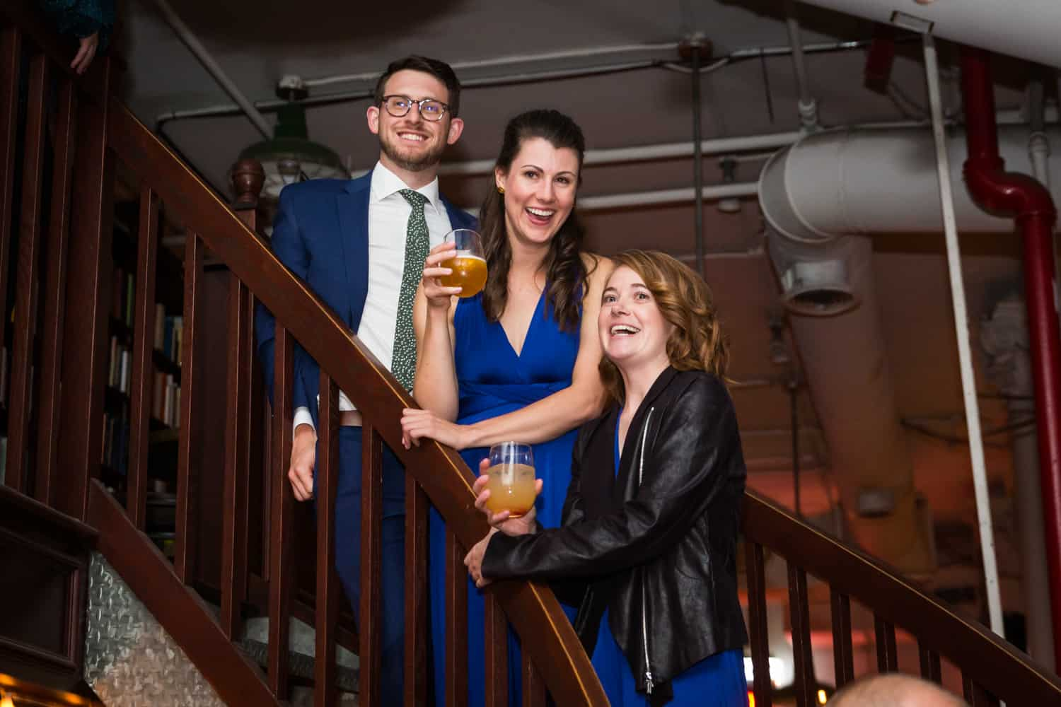 Three guests on stairs laughing at a Housing Works Bookstore Cafe wedding