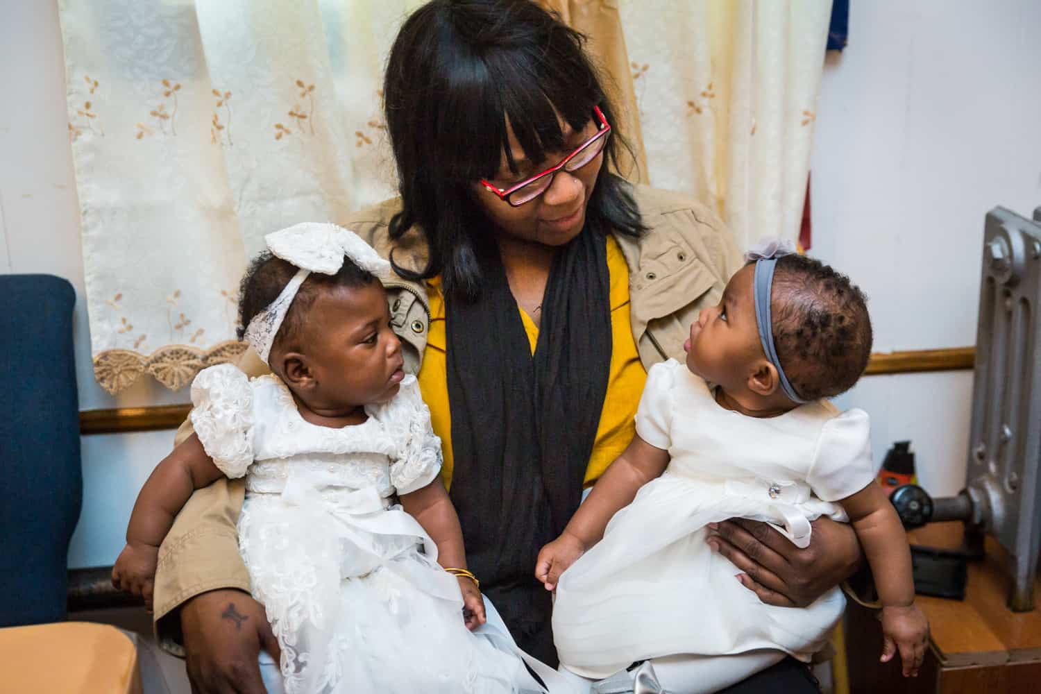 African American woman holding two little babies on her lap before Jamaica christening