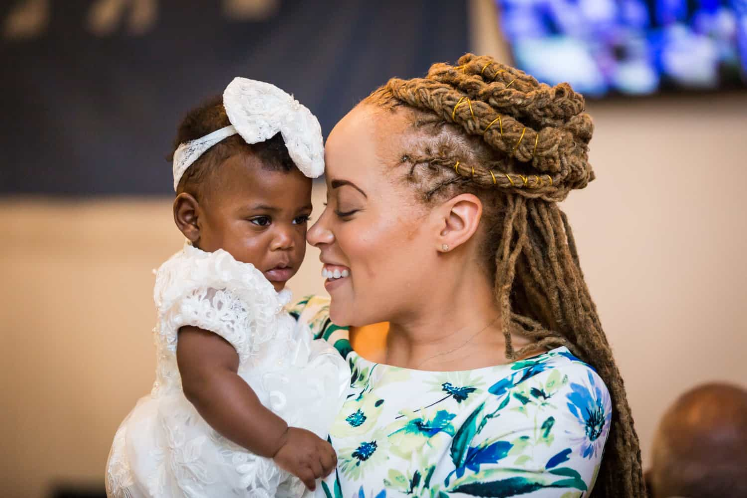 Woman with braided hair nuzzling with little baby girl