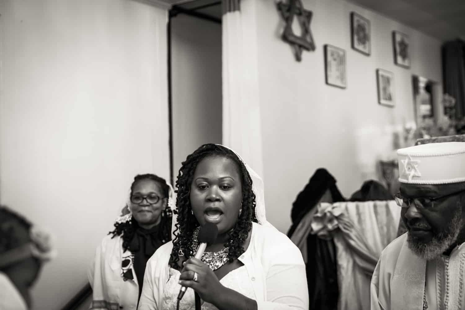 Black and white photo of woman singing during Jamaica christening