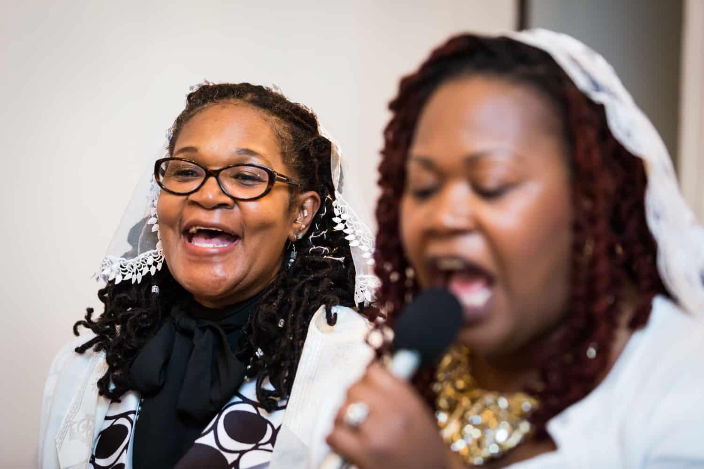 Two African American women singing during Jamaica christening