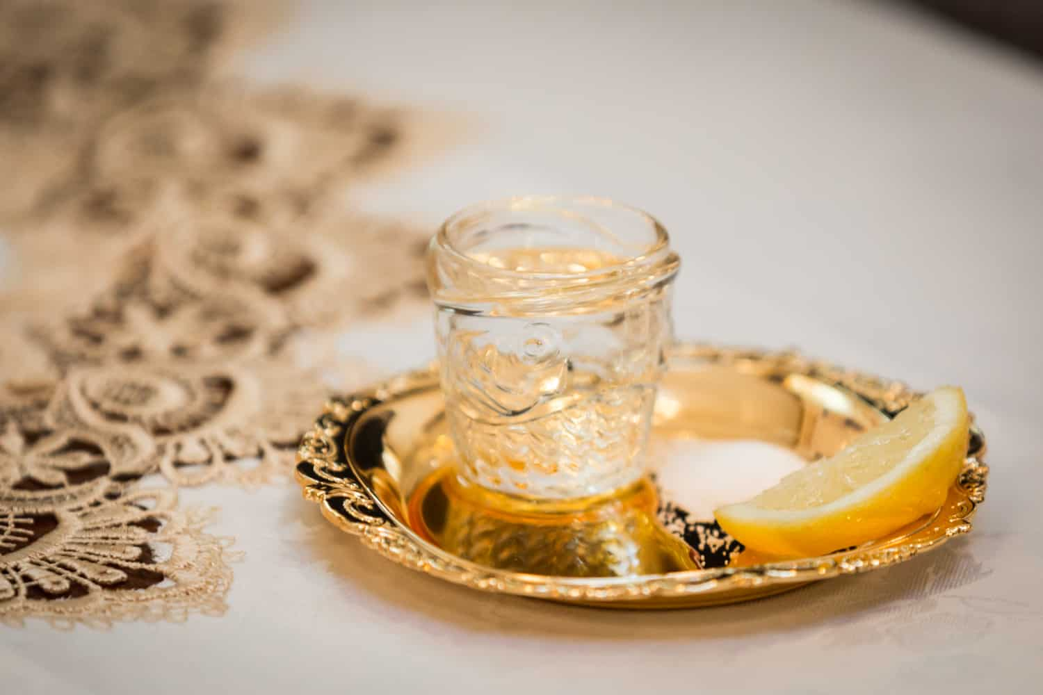 Gold plate with lemon slice and small jar of honey