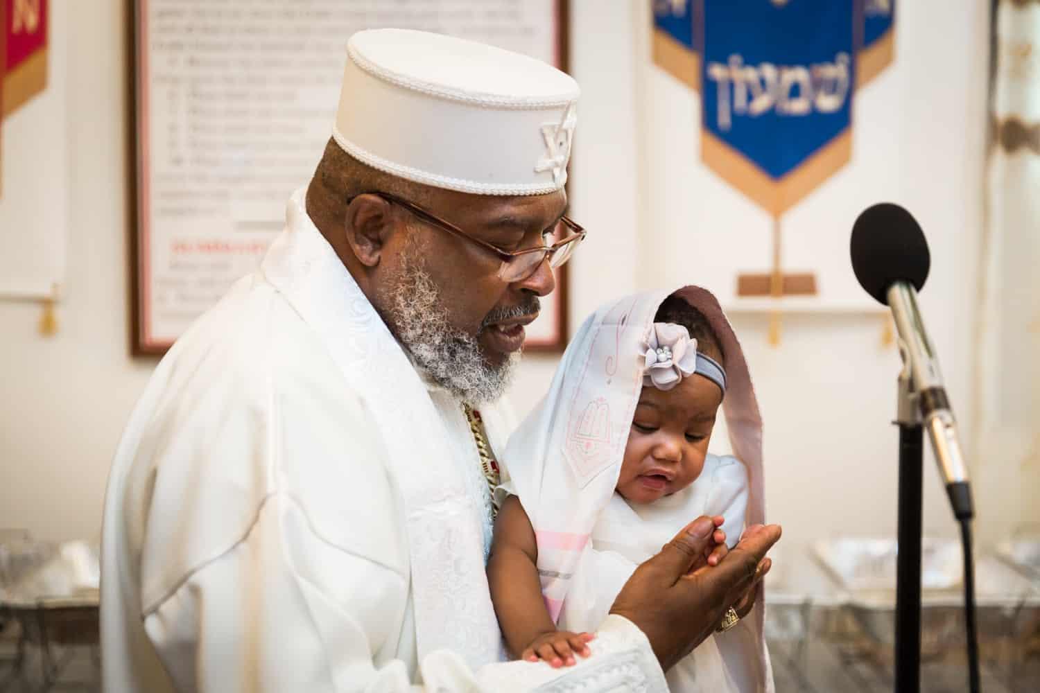 Pastor in white robe and hat holding little baby during Jamaica christening