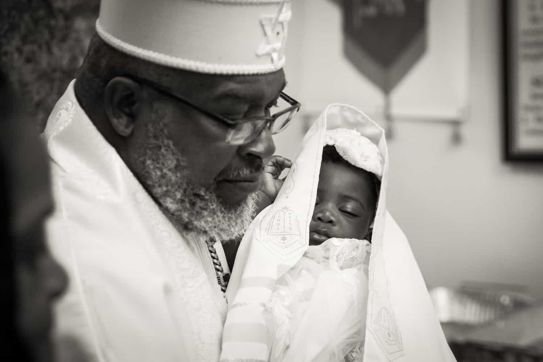 Black and white photo of pastor holding sleeping baby