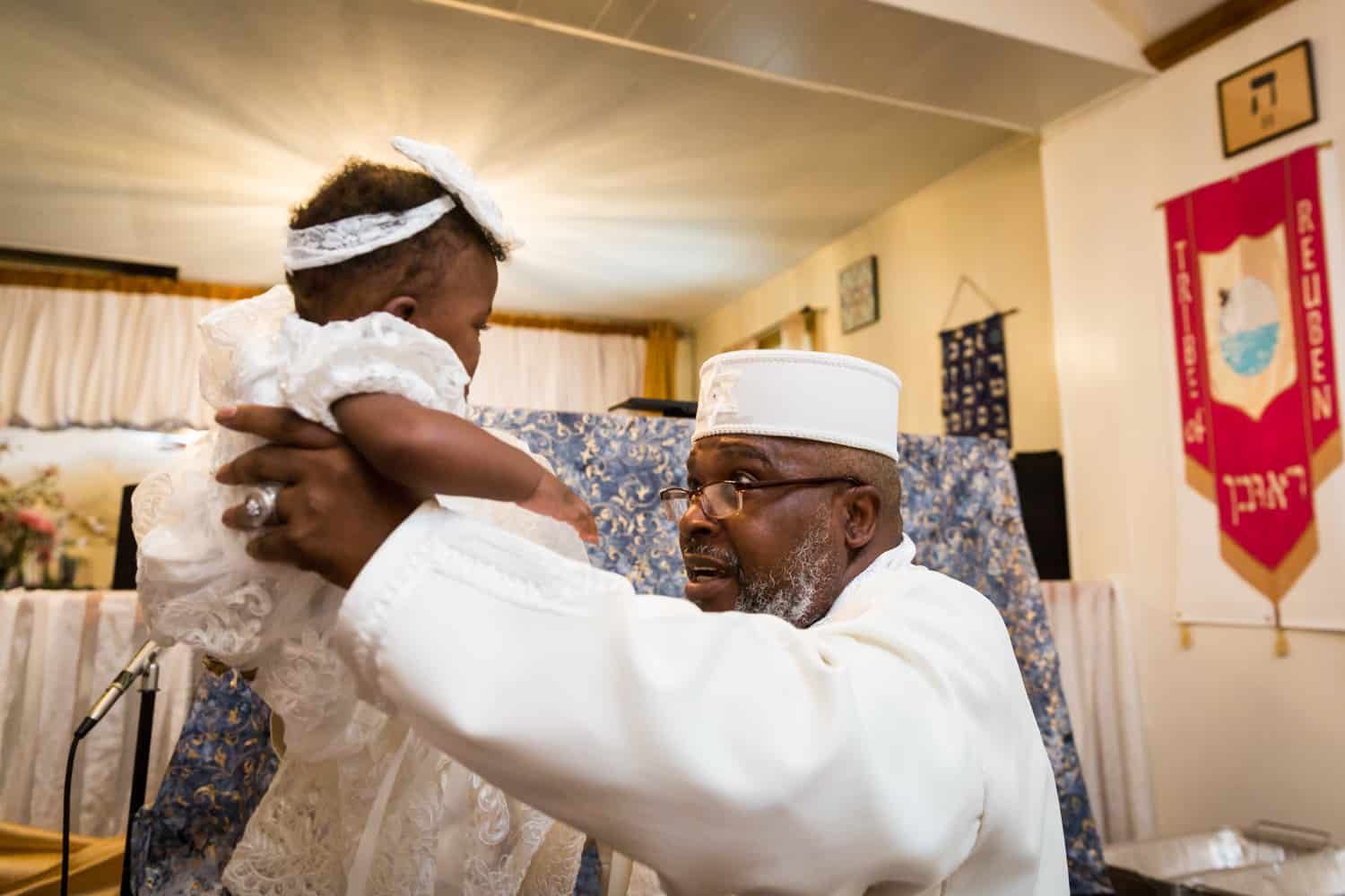 Pastor in white robes holding baby during Jamaica christening