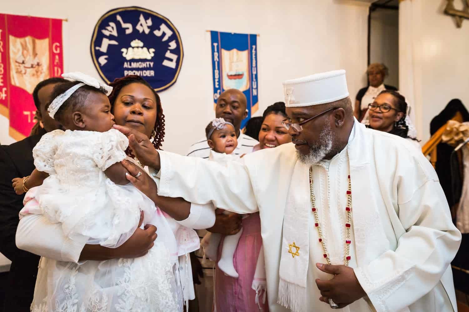 Pastor putting finger in baby's mouth during Jamaica christening
