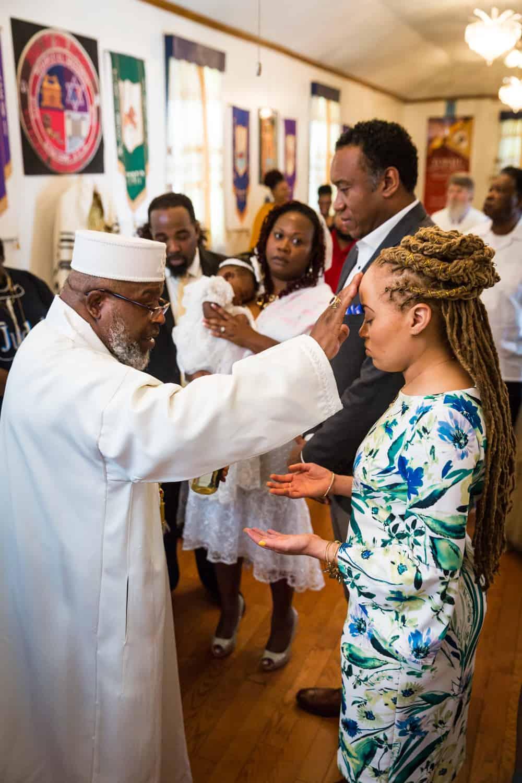 Pastor blessing family members during Jamaica christening