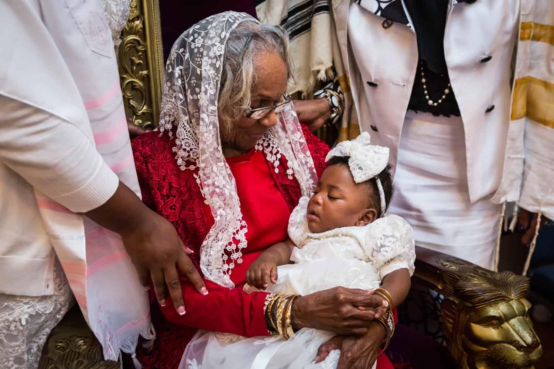 Grandmother wearing scarf over head looking at sleeping baby