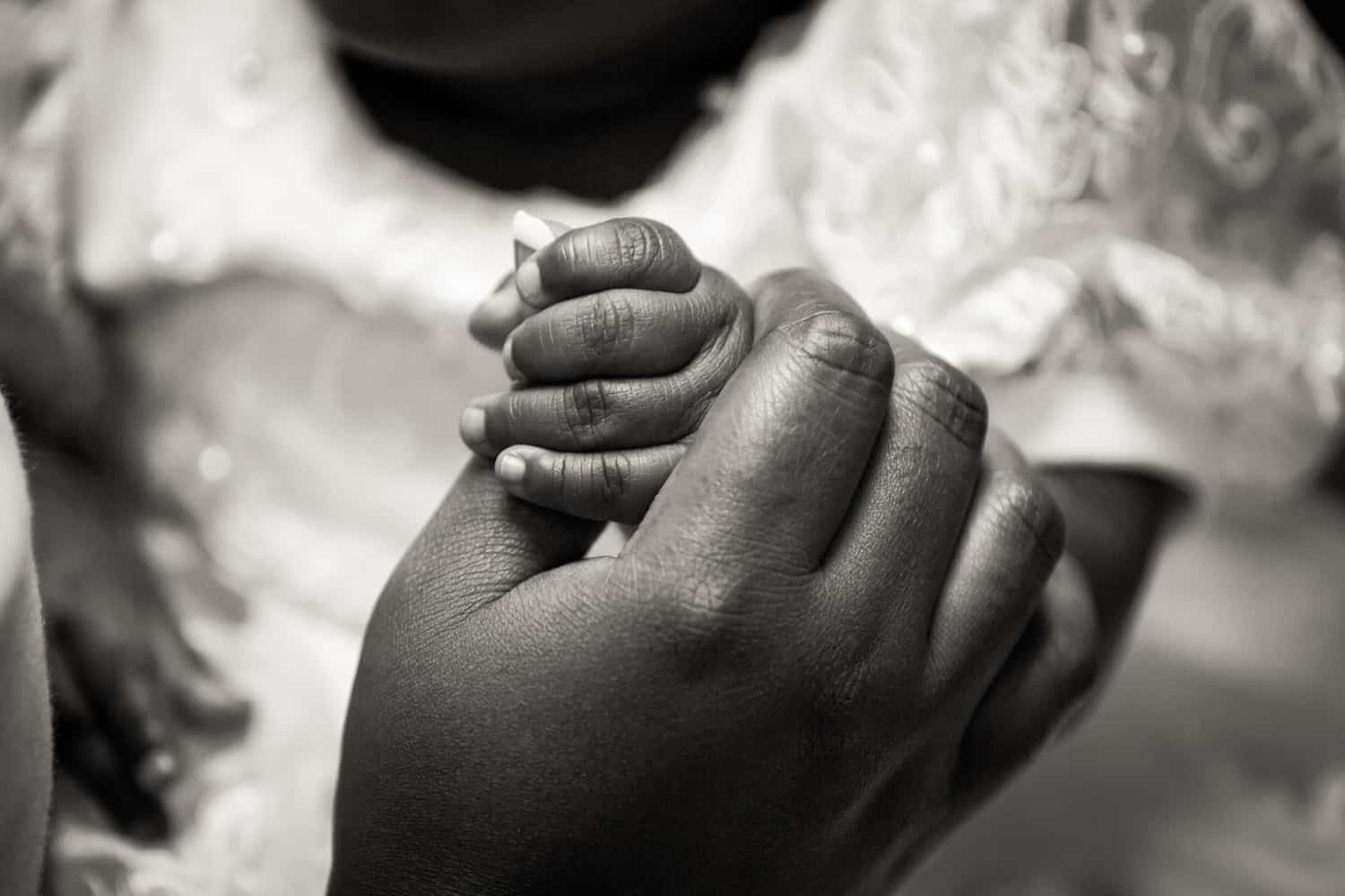 Black and white photo of mother's hand holding baby hand