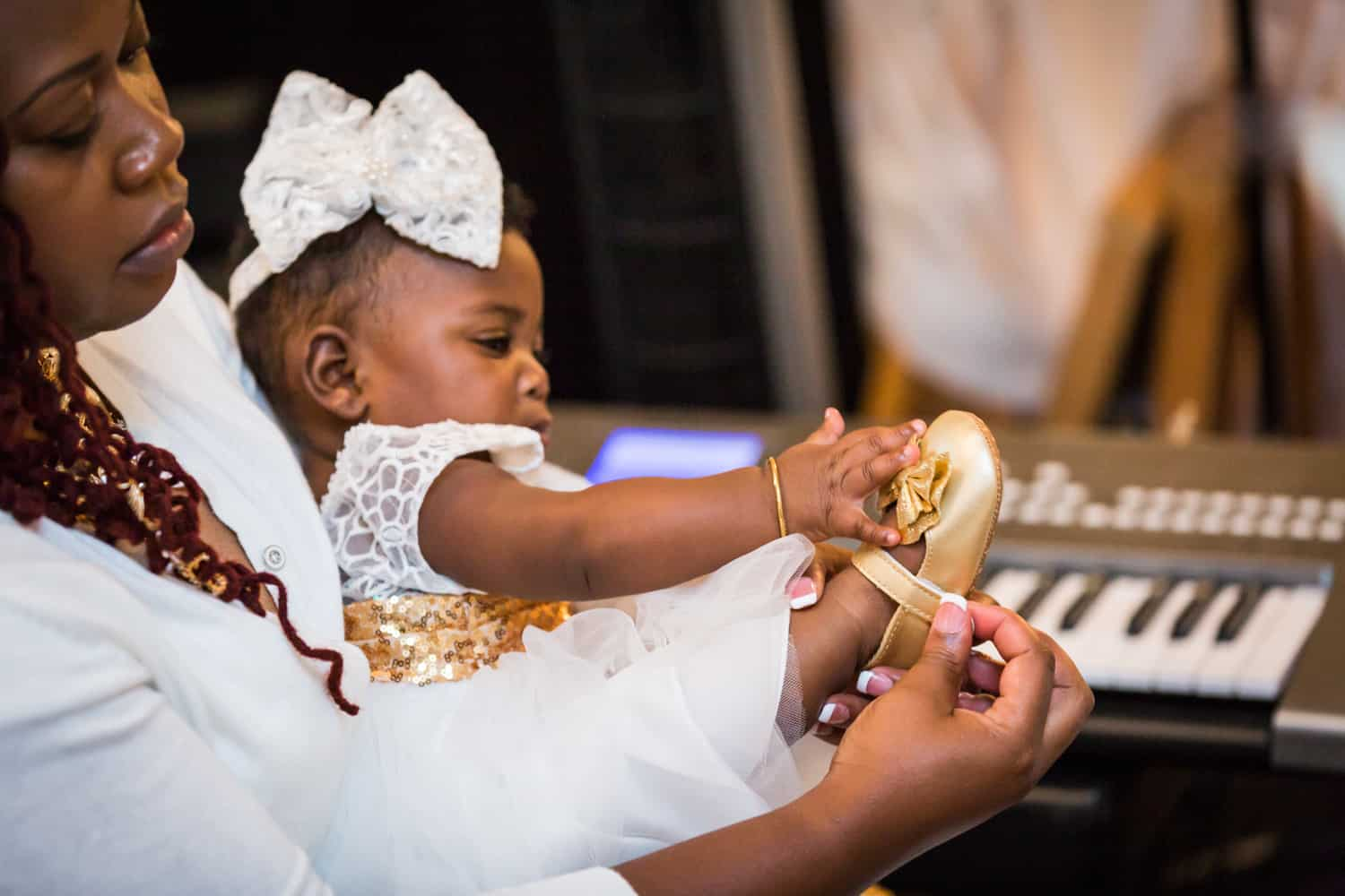 Baby girl playing with gold shoe as mother puts on shoe