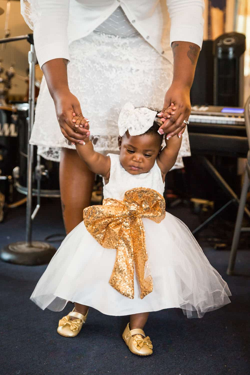 Mother's hands holding baby girl wearing white dress and gold sash