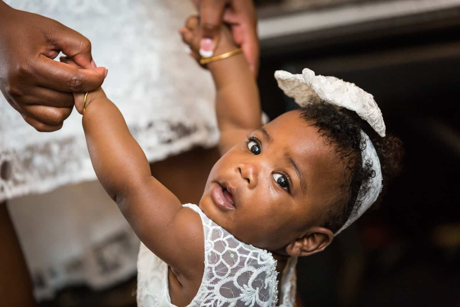 Hands holding African American baby girl wearing white dress and bow
