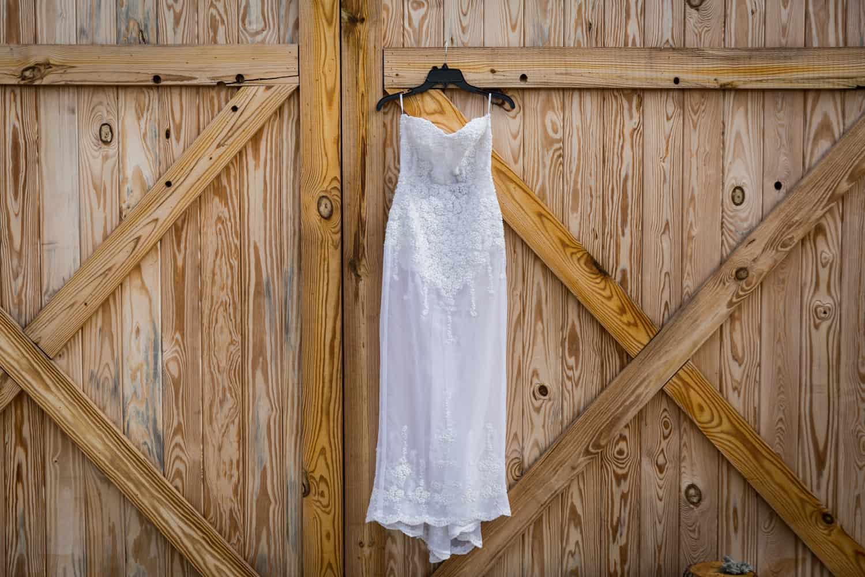 Sleeveless wedding dress on hanger in front of barn door