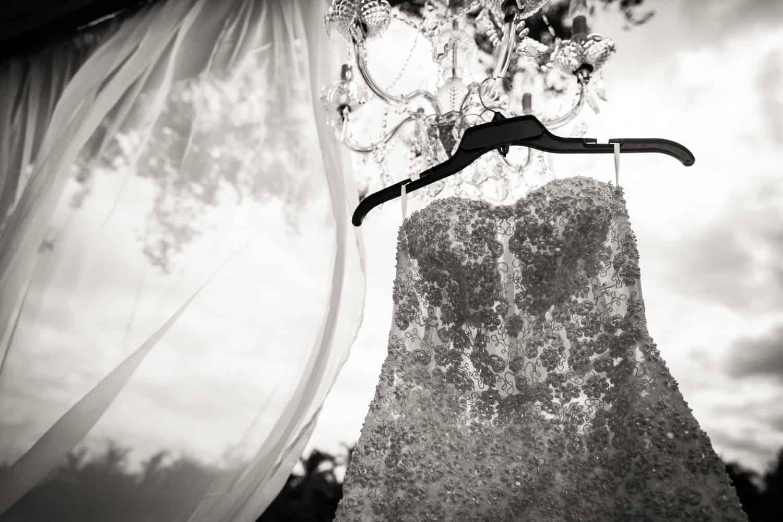 Black and white photo of sleeveless wedding dress on hanger