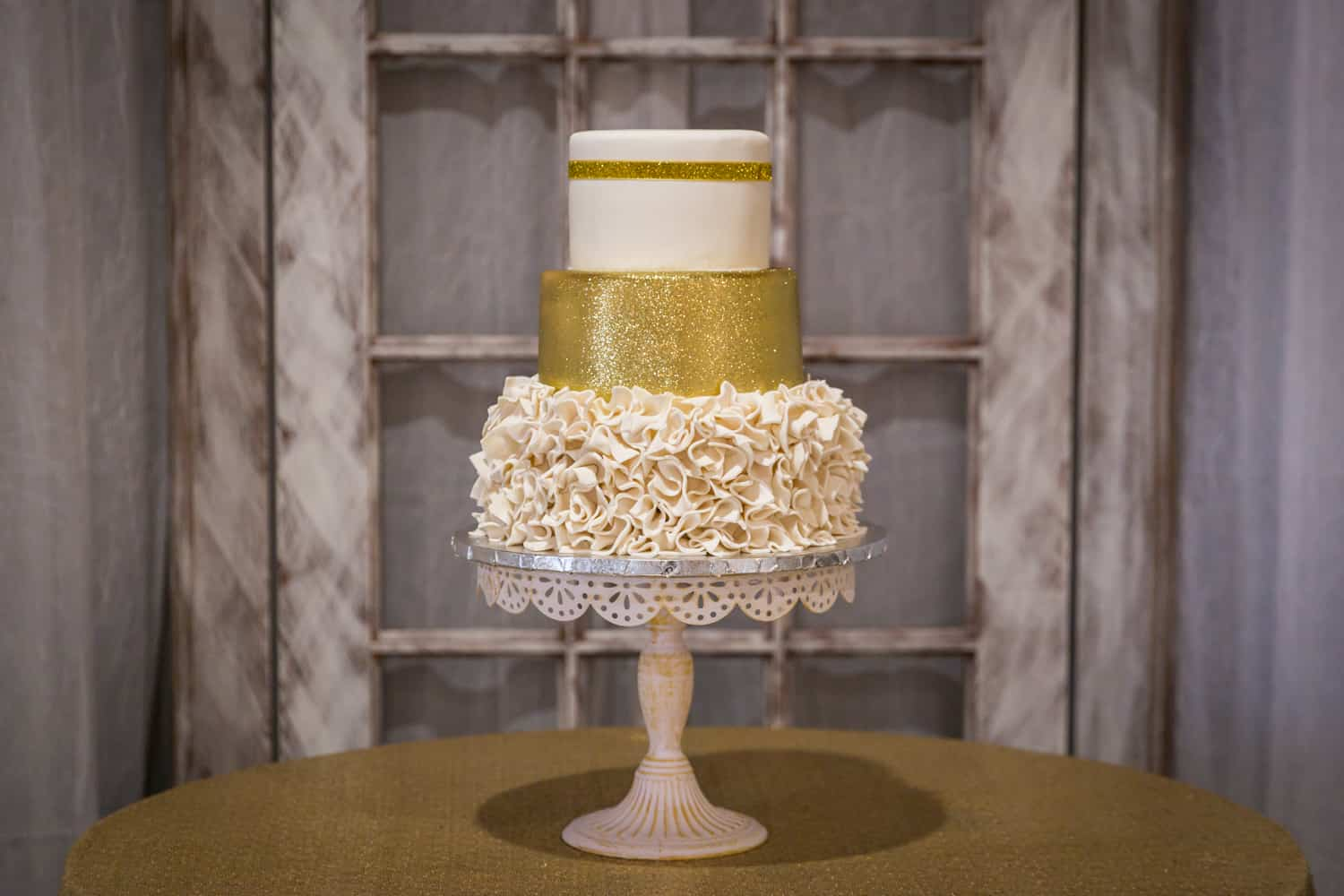 Wedding cake on cake stand with intricate icing and gold glitter