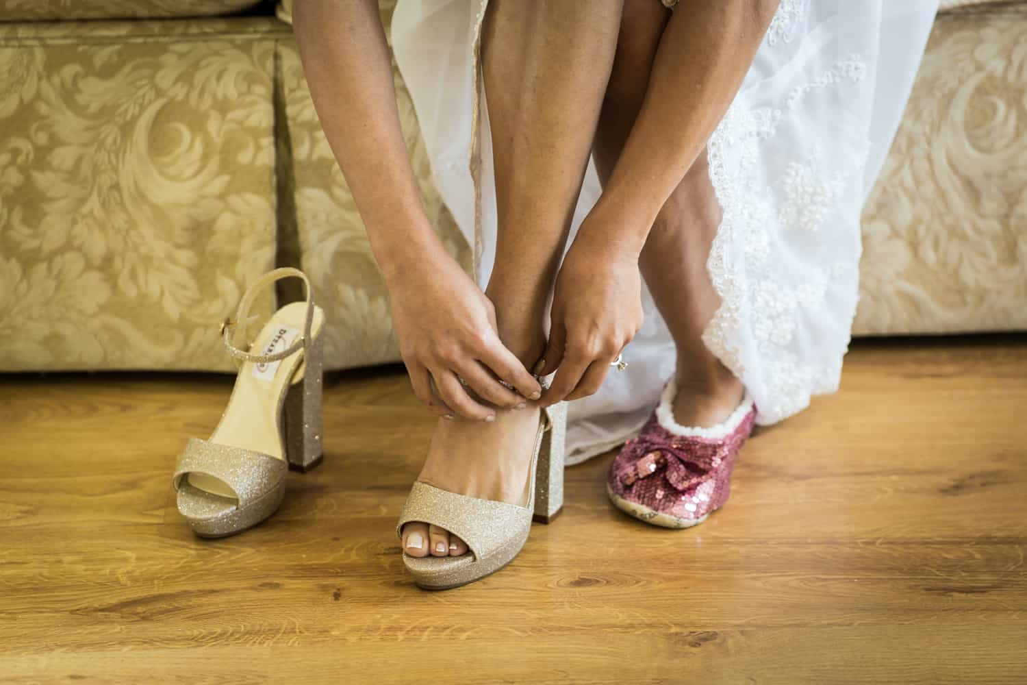 Woman's hands putting on high heel and other foot in pink sequin slipper