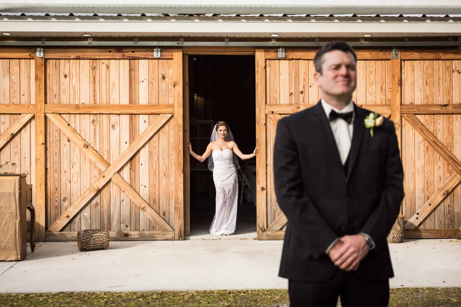 Bride looking through barn door at groom with back turned