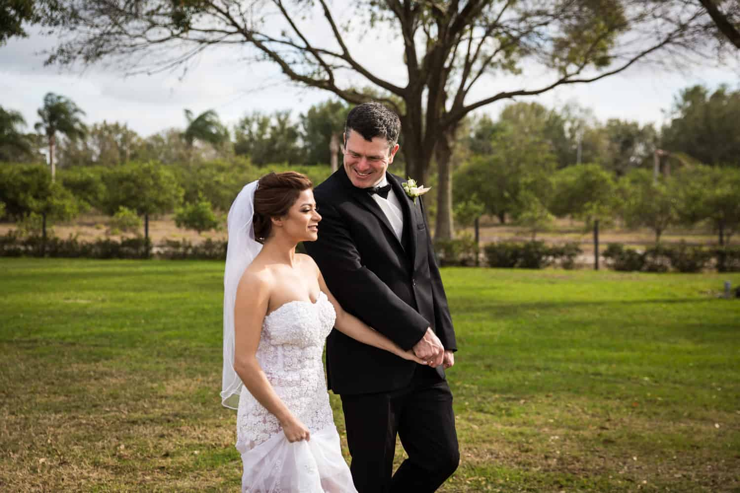 Bride and groom holding hands and walking for an article on wedding cost cutting tips