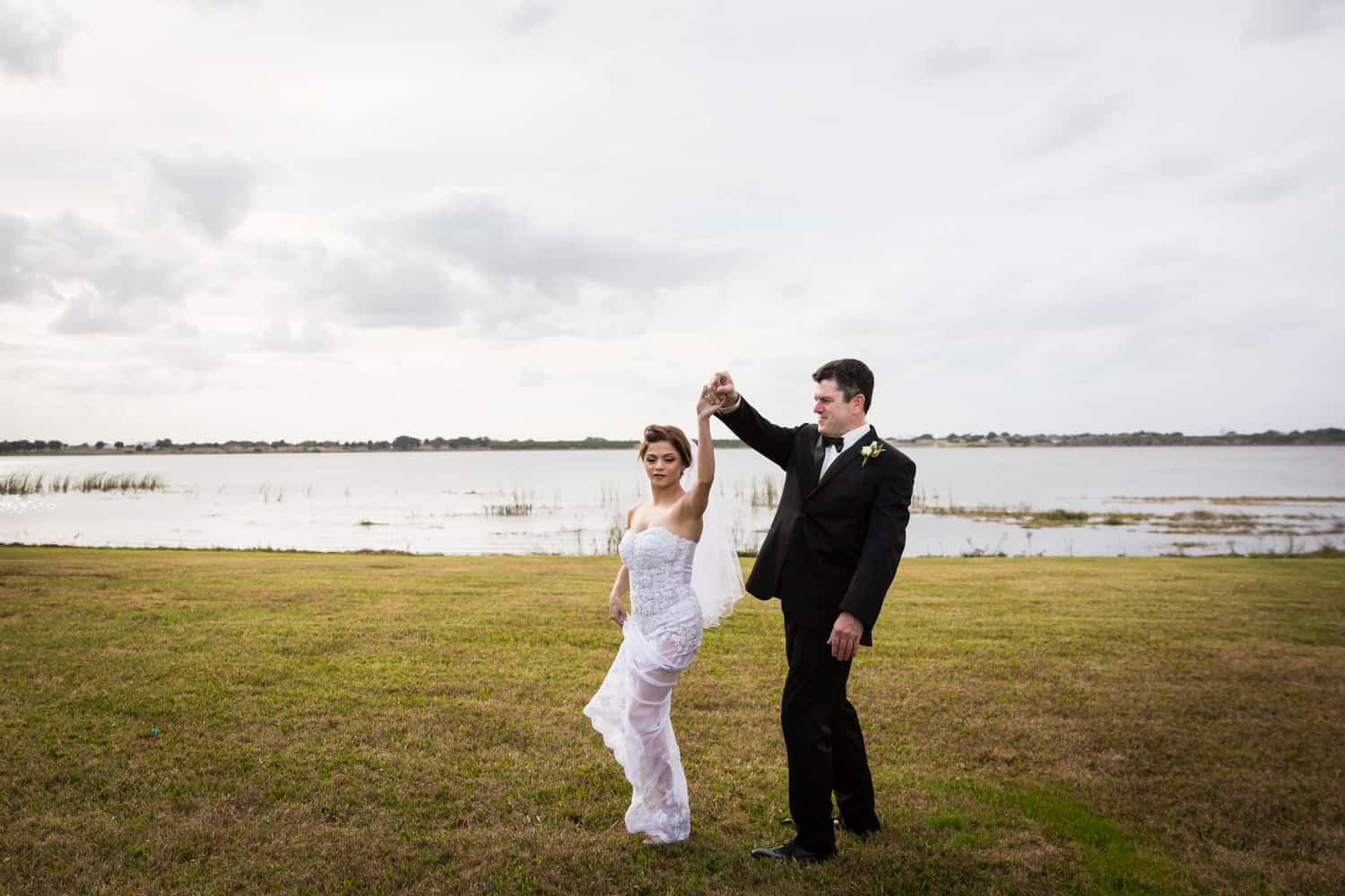 Bride and groom dancing in front of lake for an article on wedding cost cutting tips
