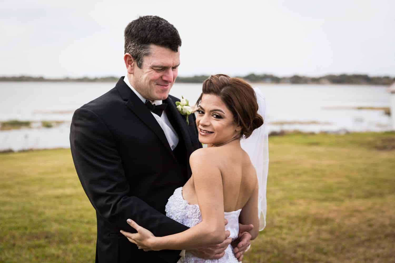 Bride and groom in front of lake for an article on wedding cost cutting tips