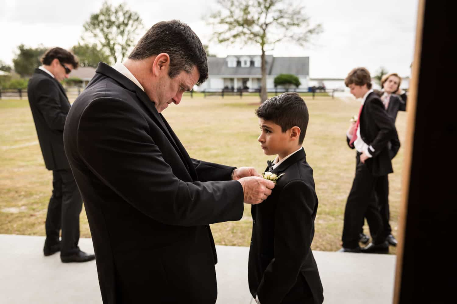Groom adjusting the handkerchief of young boy for an article on wedding cost cutting tips