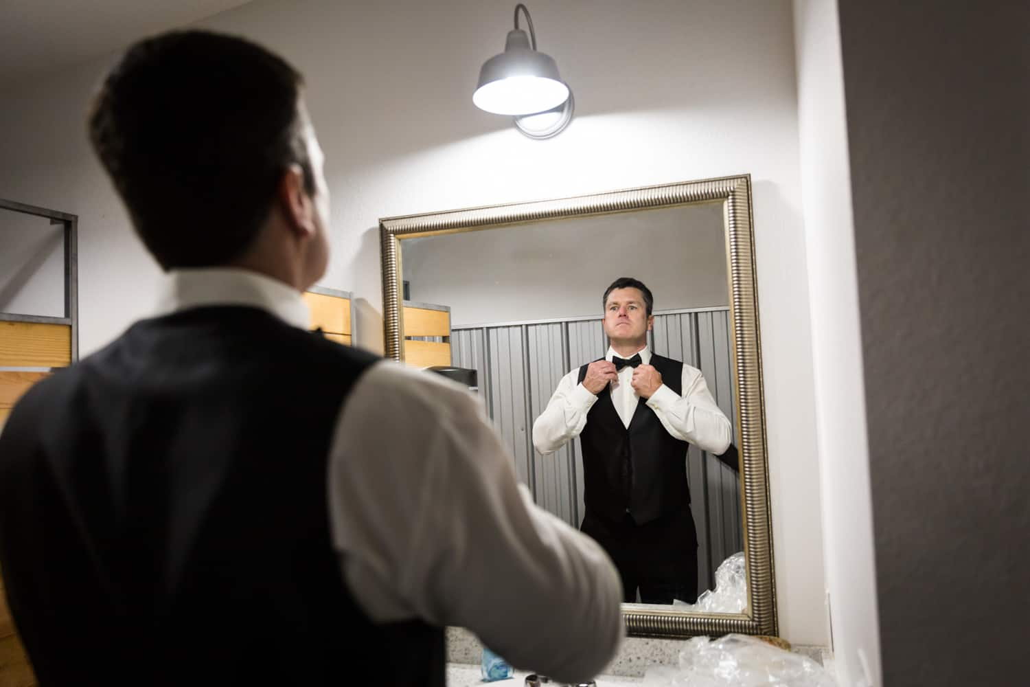 Groom adjusting bowtie in mirror for an article on wedding cost cutting tips