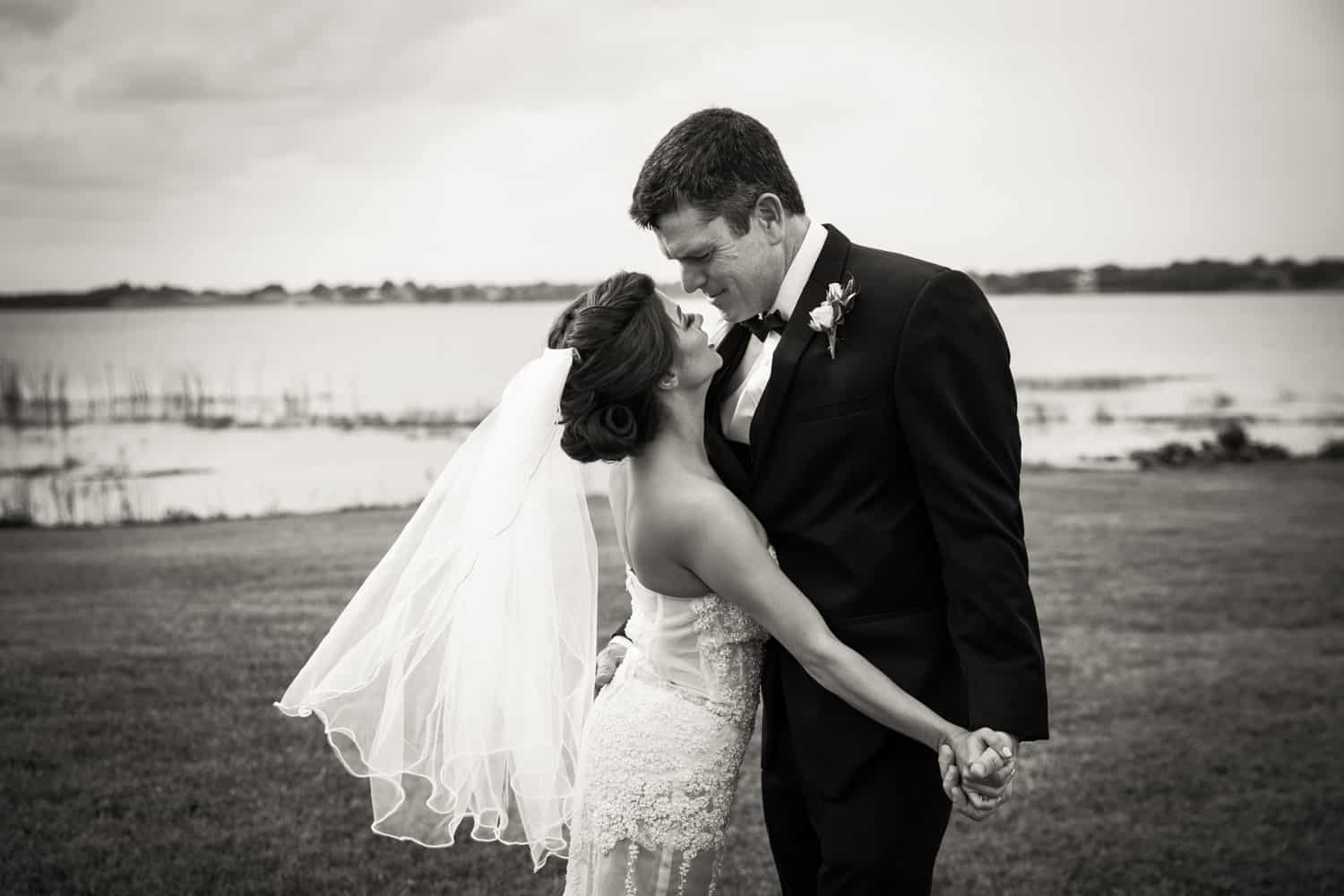 Black and white photo of bride and groom holding hands in front of lake for an article on wedding cost cutting tips