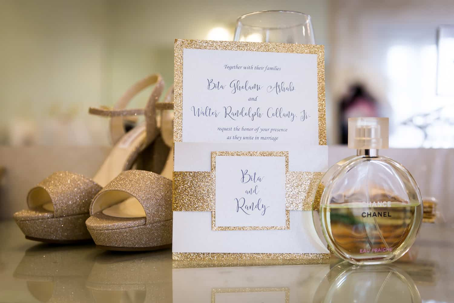 Invitation with gold glitter and perfume bottle for an article on wedding cost cutting tips