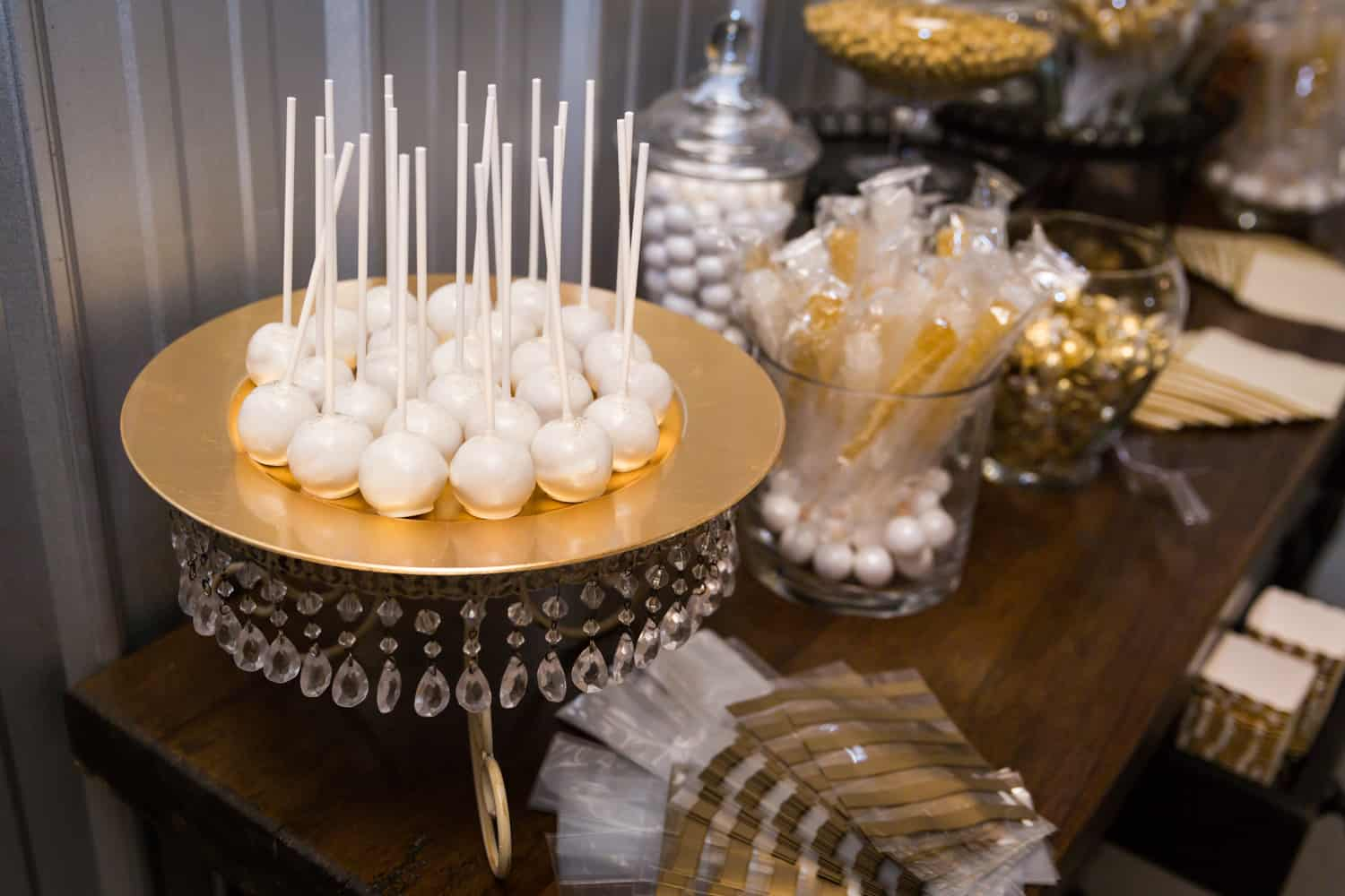 Plate of white cake pops and bowl of candies