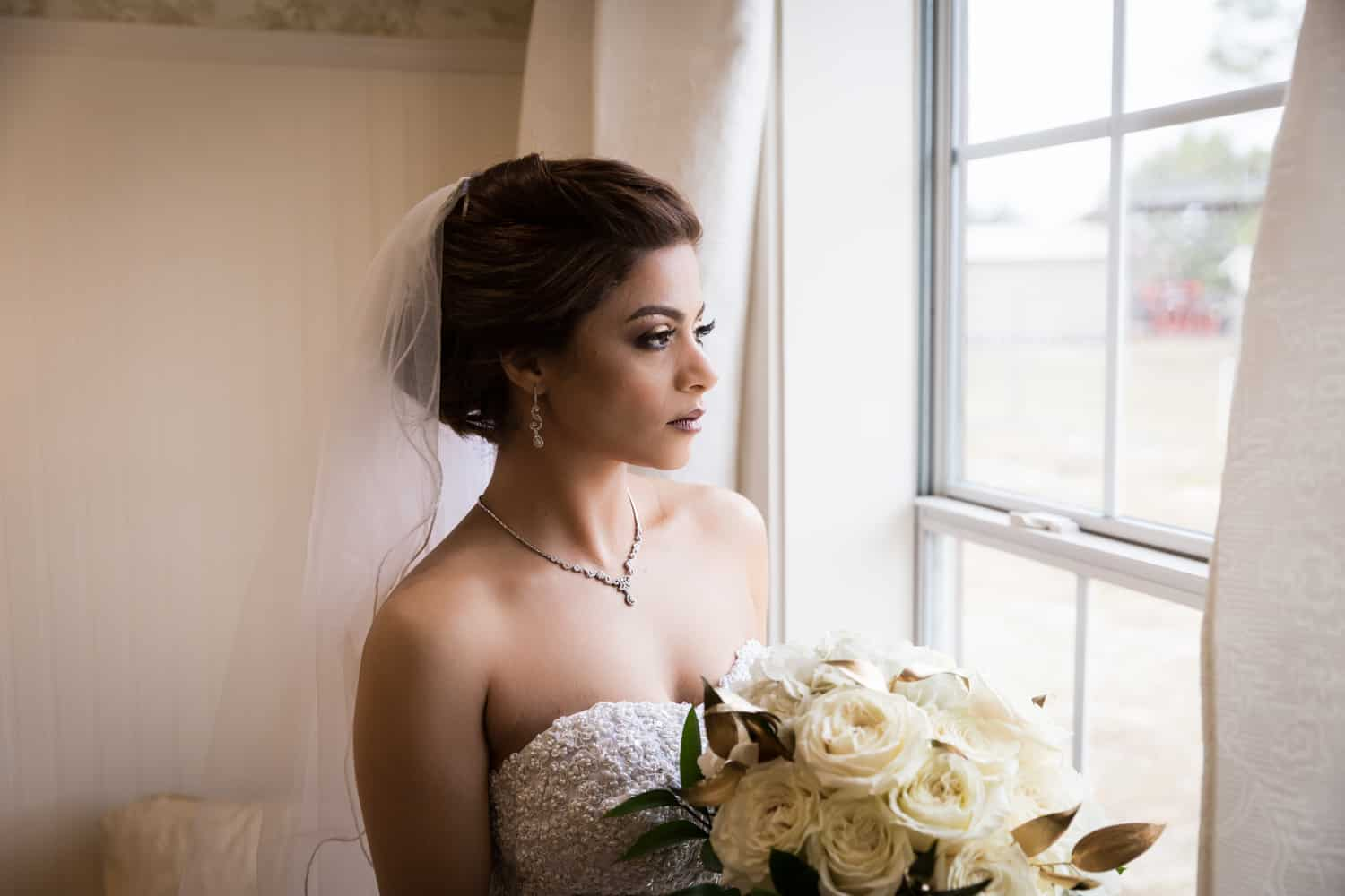 Bride holding bouquet and looking out window for an article on wedding cost cutting tips