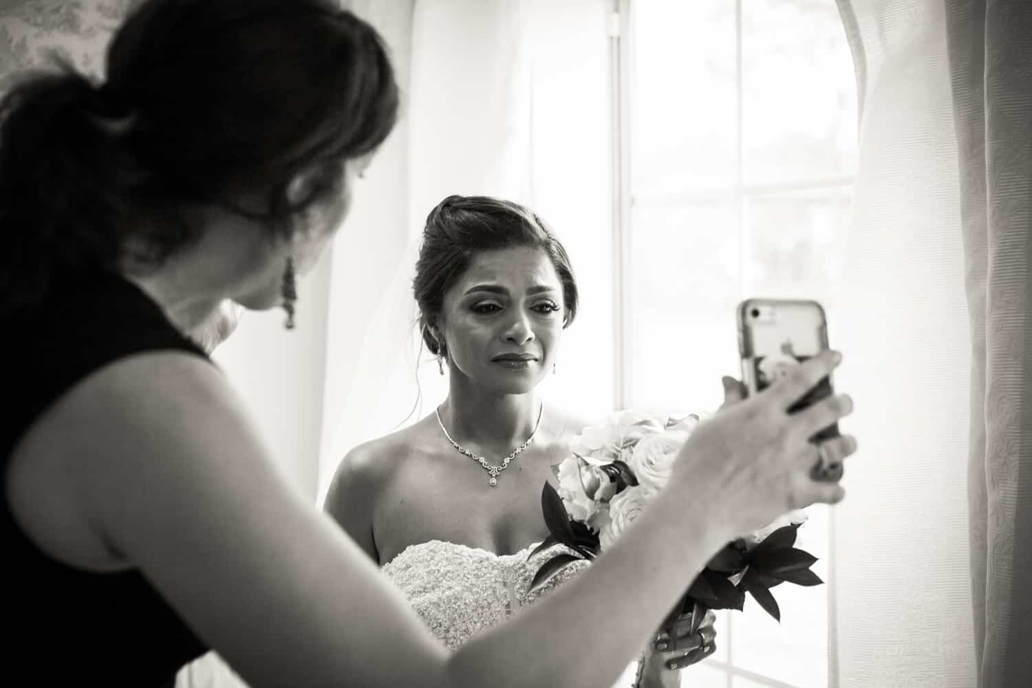 Black and white photo of bride crying and watching cell phone