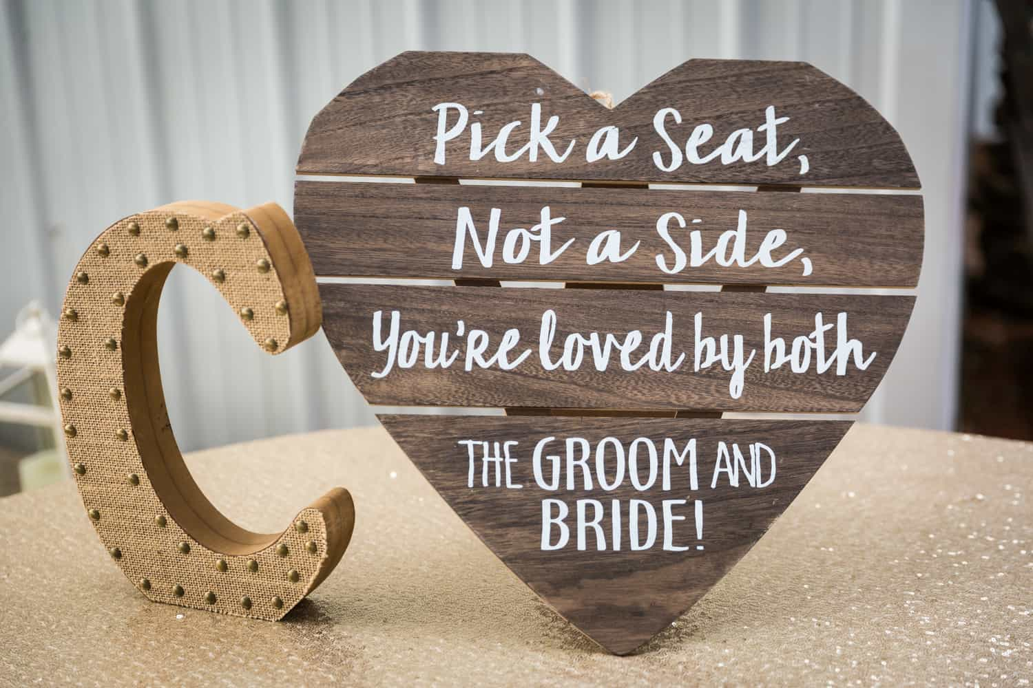 Seating sign for guests on heart-shaped wood