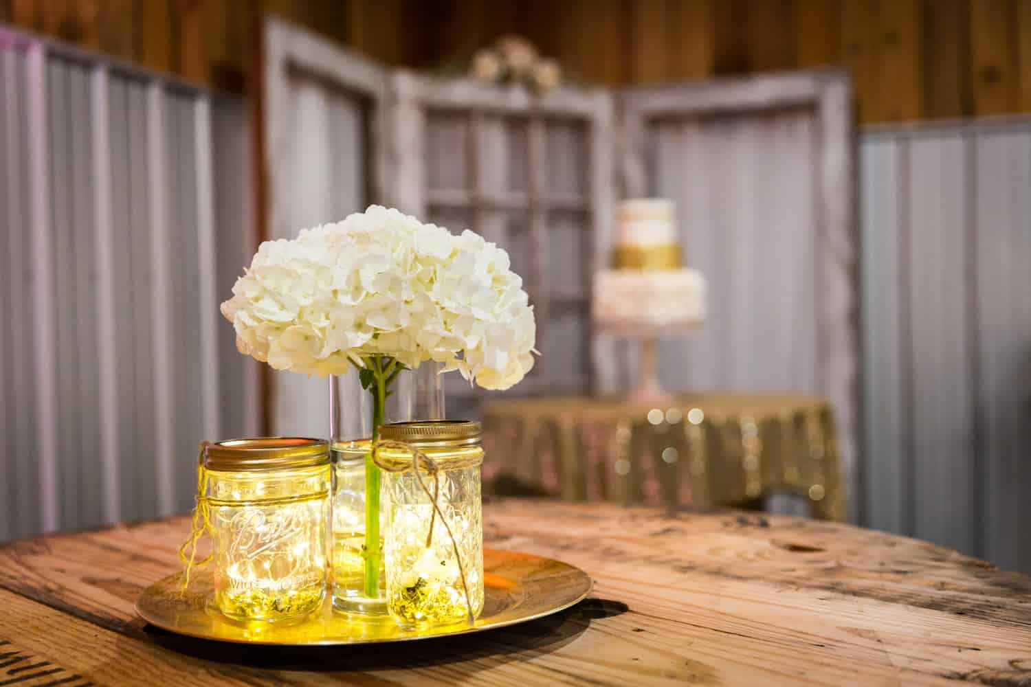 Tray of mason jars filled with fairy lights and vase of white hydrangeas