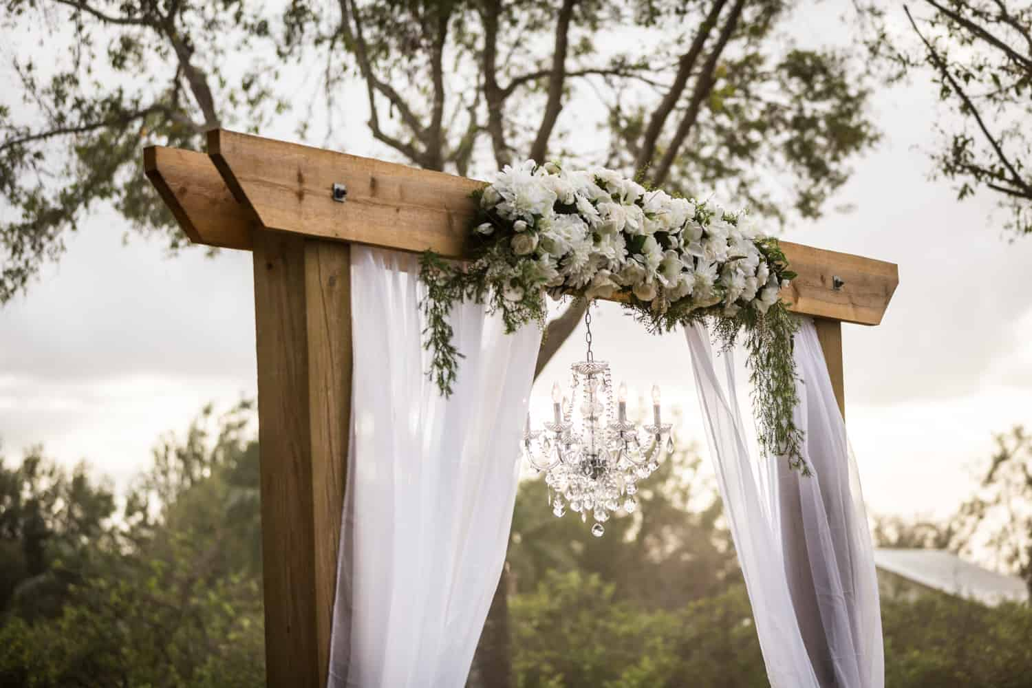Wooden archway with white curtains, flowers, and a chandelier